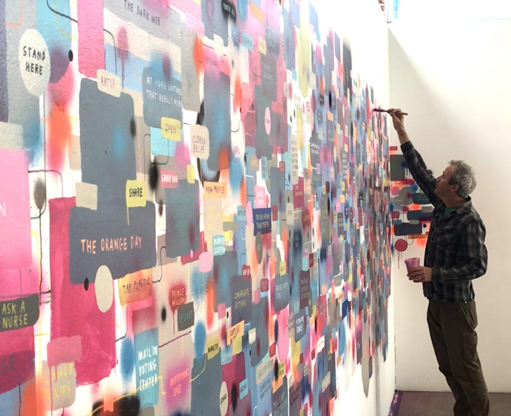 Tucker Nichols painting the mural